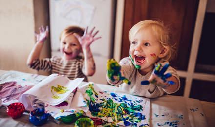 Twee kinderen spelen met hun rommelige handen met een kunstenaarspalet en blauwe verf
