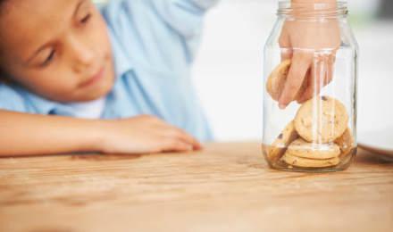 Een kind reikt in een glazen koekjespot op een houten tafel om een koekje te pakken