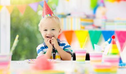 Kind viert verjaardag met verjaardagshoedje op aan een versierde verjaardagstafel