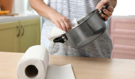 Een persoon naast het aanrecht en maakt een pot schoon met een vel keukenpapier