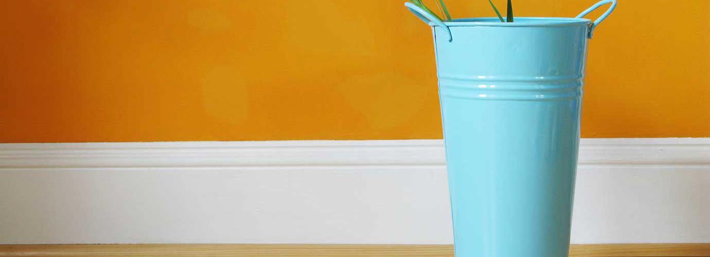 Plinthe blanche séparant un plancher en bois et un mur orange