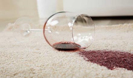 Verre à vin renversé sur un tapis créant une tache de vin