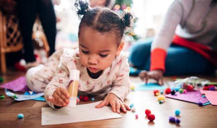 Een klein meisje houdt een lijmstift vast terwijl ze knutselt
