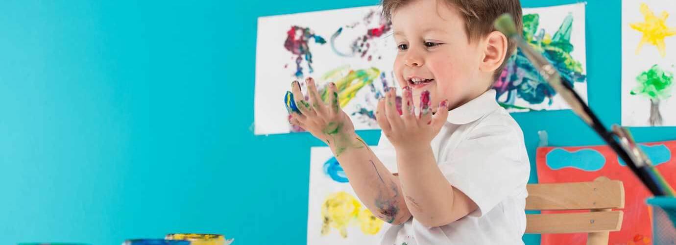 Een kind zit aan tafel en verft met zijn vingers