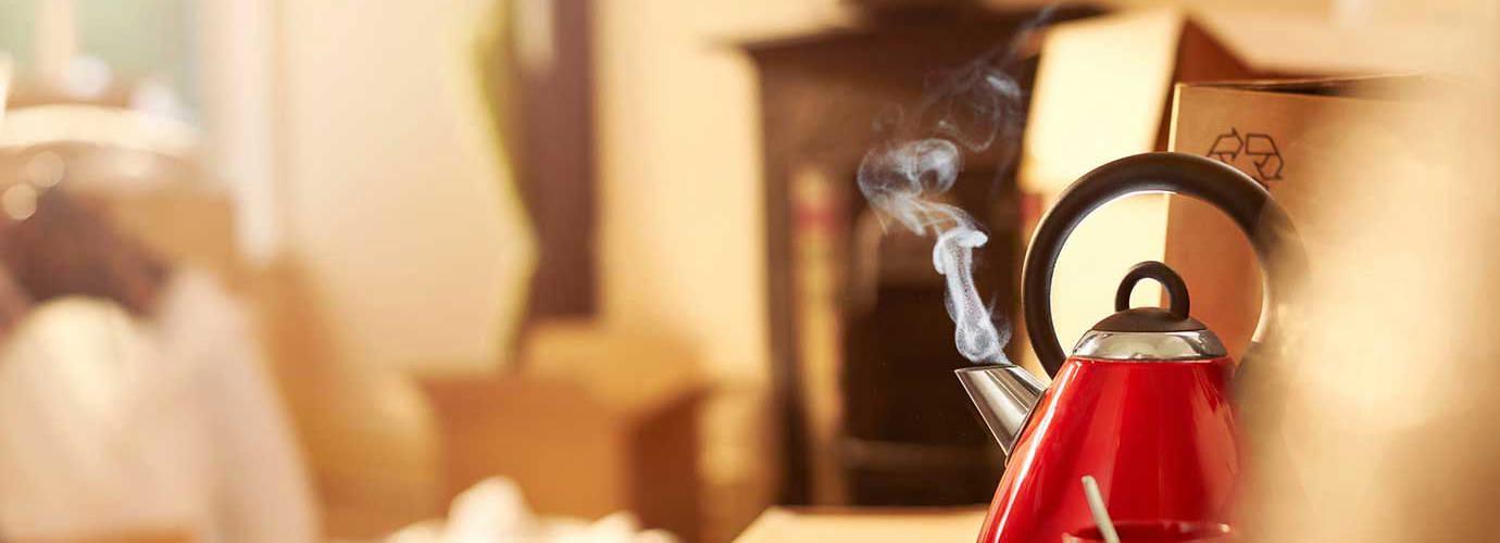 Een schone, rode ketel staat te koken op het aanrecht
