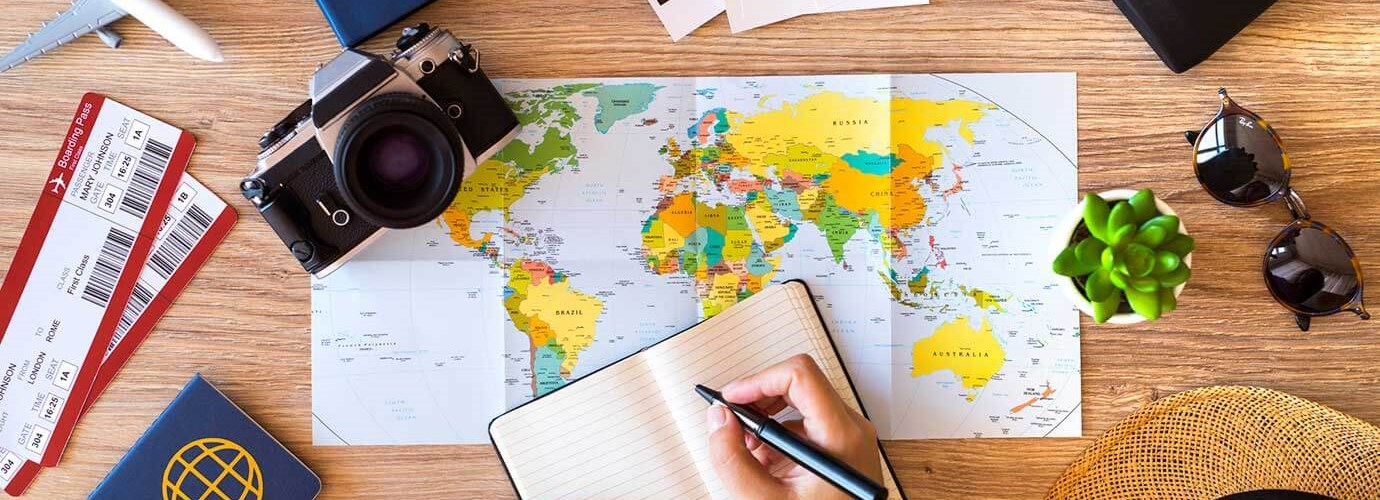 Een tafel met paspoorten, kaarten, zonnebrillen, notitieboekje, vliegtickets en een planner
