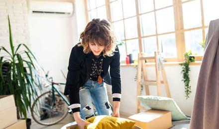 Vrouw uit pakt een kartonnen doos uit tijdens het opruimen van het huis