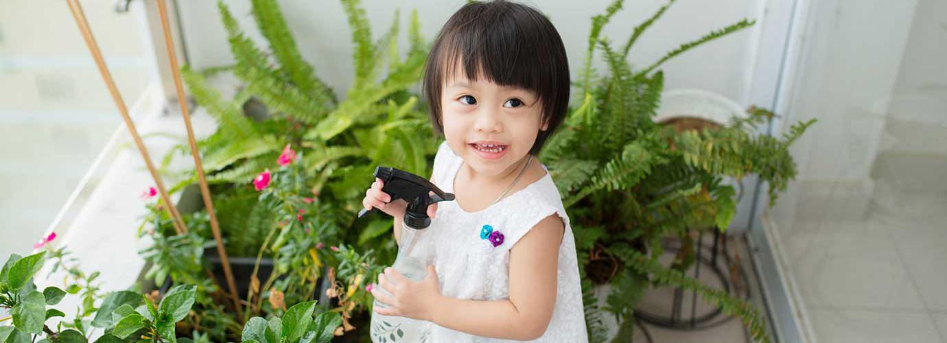 Klein meisje verzorgt kamerplanten