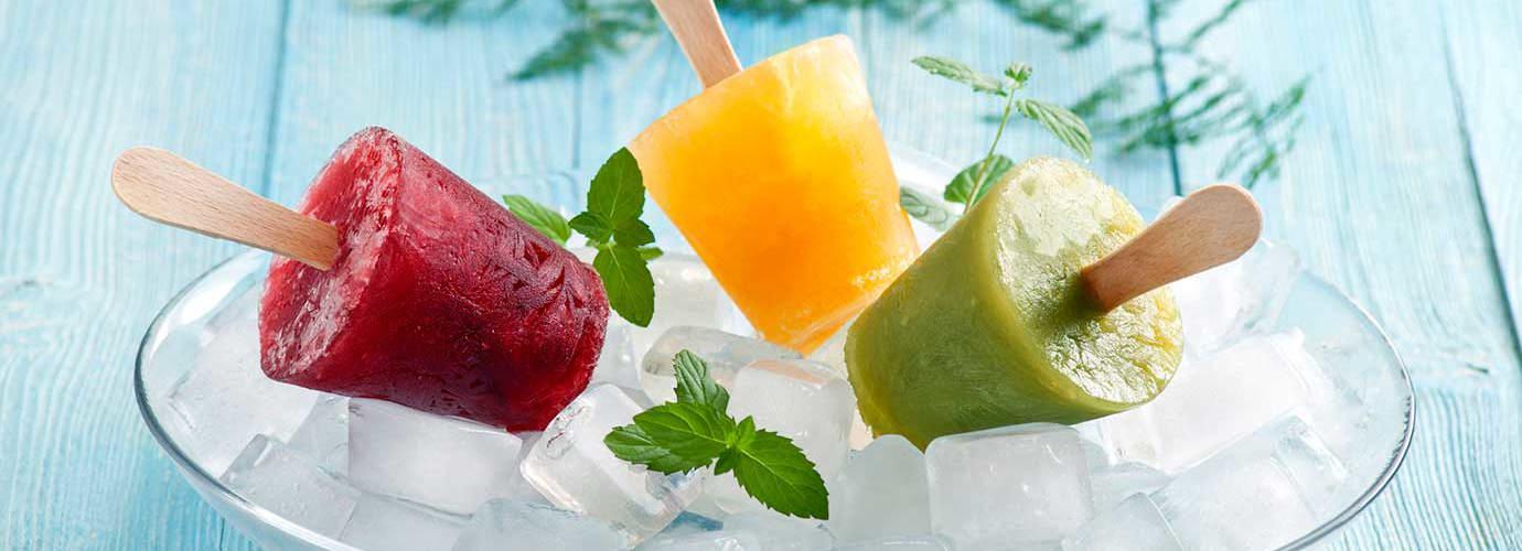 Drie fruitijsjes op een plek bedekt met ijsblokjes