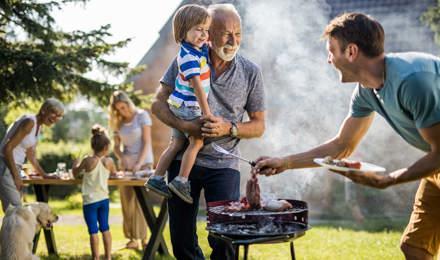 Un homme prépare un barbecue dans le jardin