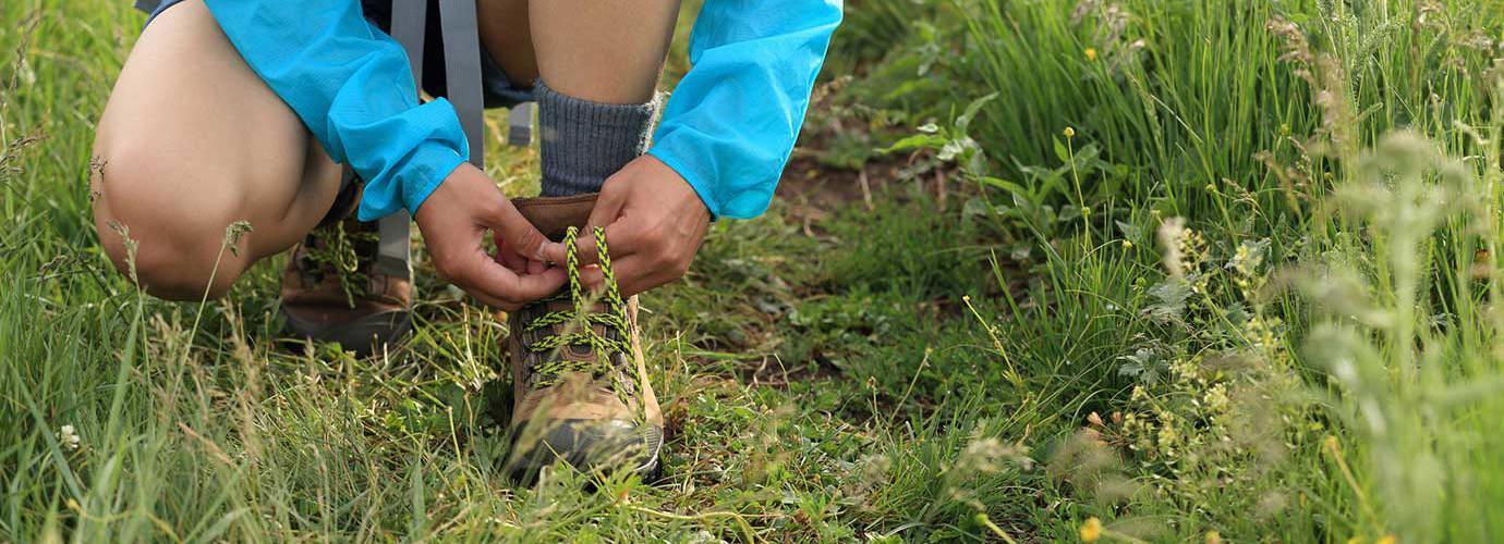 Un enfant attache ses lacets de chaussures de marche