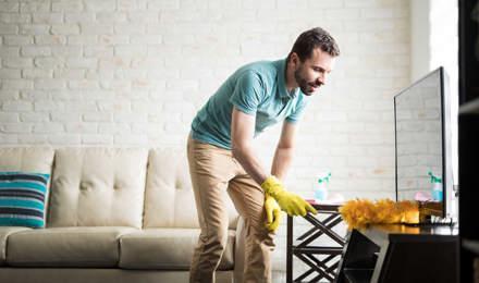 Un homme dépoussière sa maison avec un chiffon