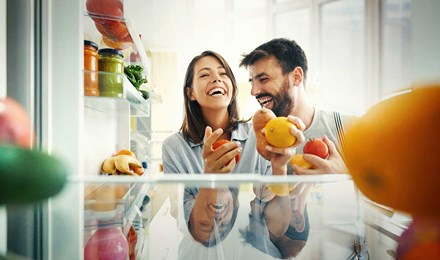 Un couple prend des fruits et des légumes dans le réfrigérateur