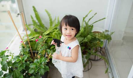 Une petite fille prend soin des plantes d'intérieur