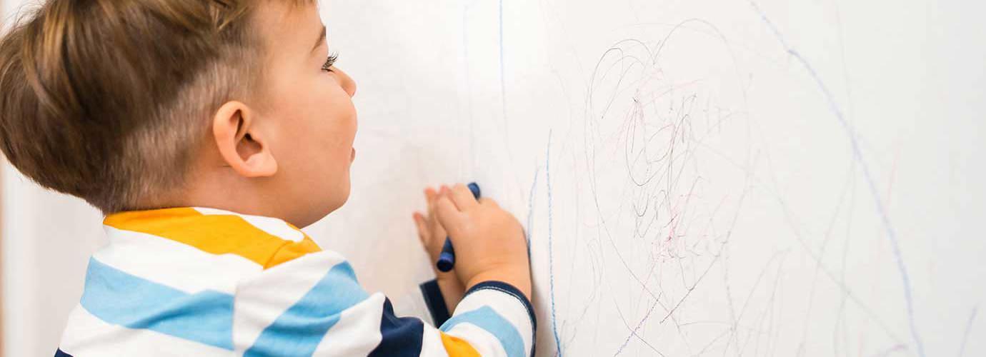 Un bébé dessine sur un papier peint propre avec des crayons
