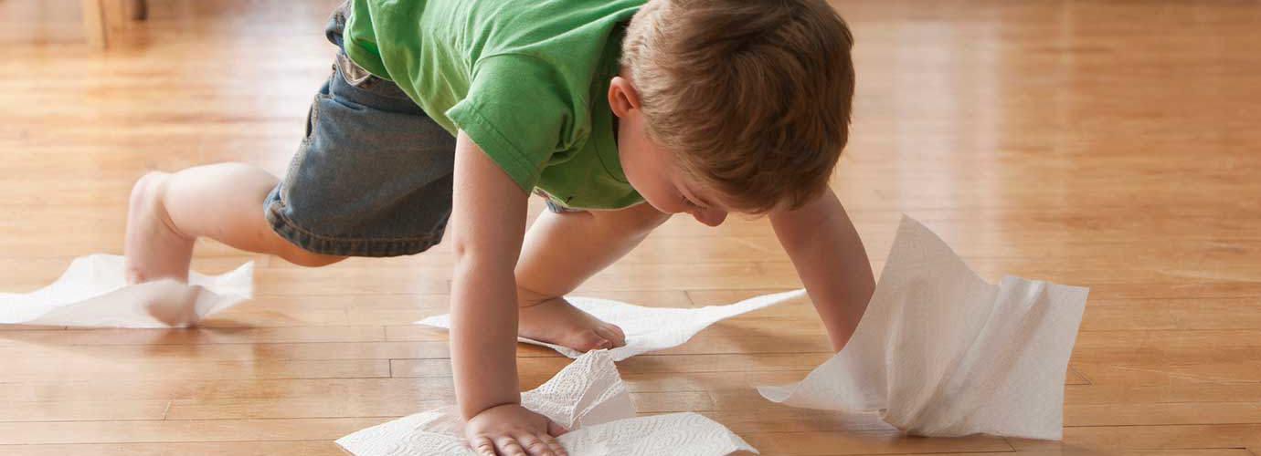 Un enfant nettoie le sol avec des essuie-tout