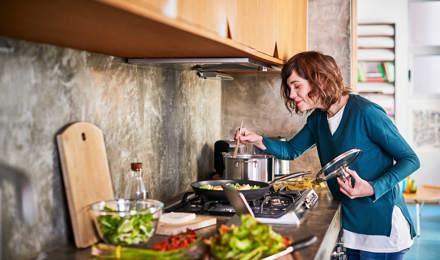 Une femme prépare la nourriture dans une cuisine et fouettant dans une casserole