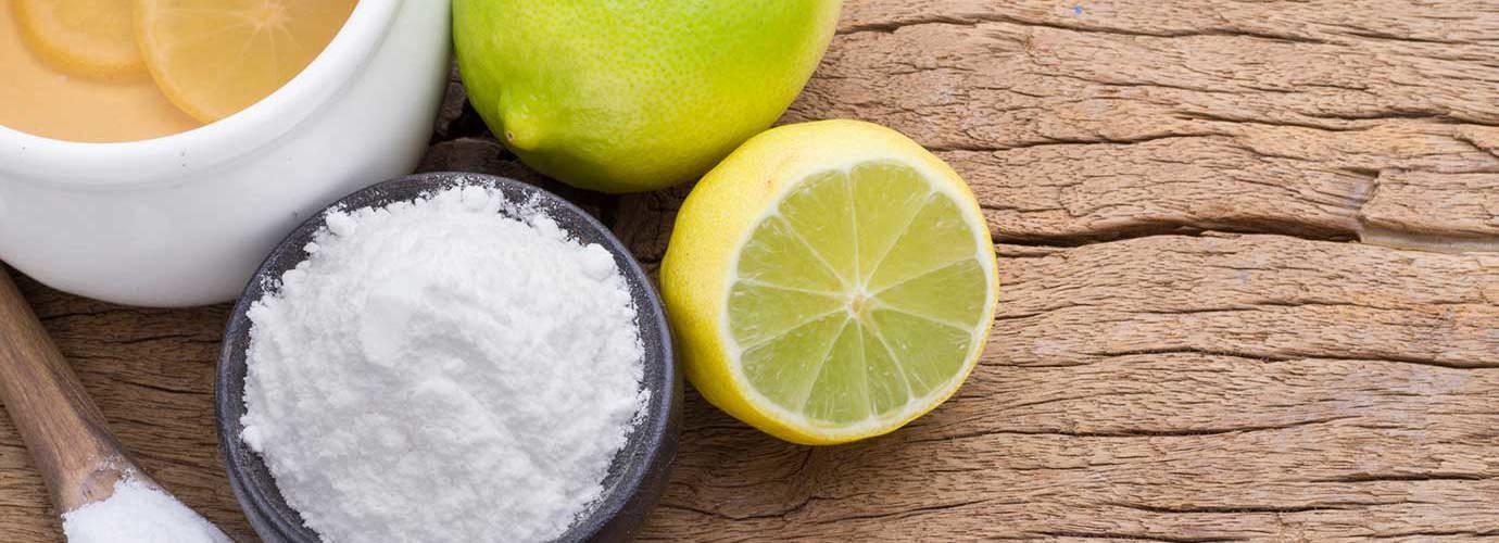 Eco produits de nettoyage tels que le citron, la chaux et le bicarbonate de soude sur une planche à découper en bois